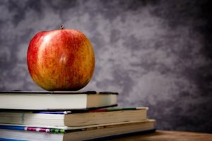stack of school books and an apple