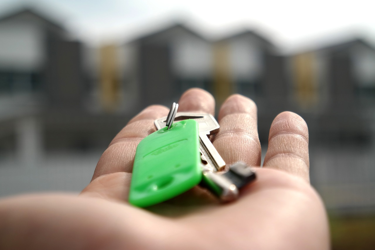 Blurry background of a new home with a hand holding keys.